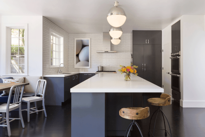 Huge frosted glass balls pendants hung over a navy bluish gray peninsula in this white kitchen. It is paired with wooden counter stools over dark hardwood flooring.