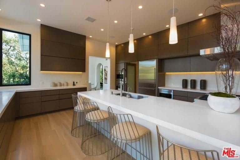 Kitchen with brown cabinetry and white peninsula lined with metal chairs over hardwood flooring. It is illuminated by modern pendants along with recessed ceiling lights.