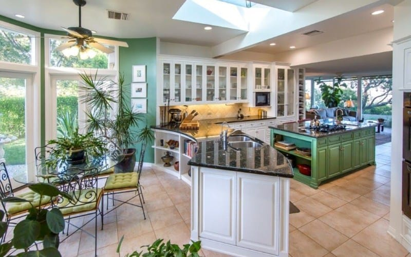 Fresh and airy kitchen features white cabinetry and green breakfast island. It has a curved peninsula with built-in shelves facing a round dining set filled with potted plants that add a tropical feel in the room.