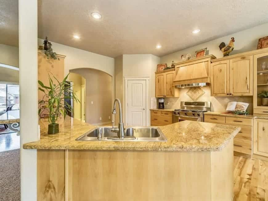 Warm kitchen offers light hardwood flooring that complements the cabinetry and peninsula topped with marble counter.