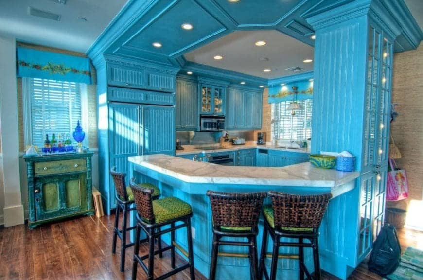 Cool blue kitchen features tray ceiling and white marble countertop along with green cushioned rattan counter chairs.