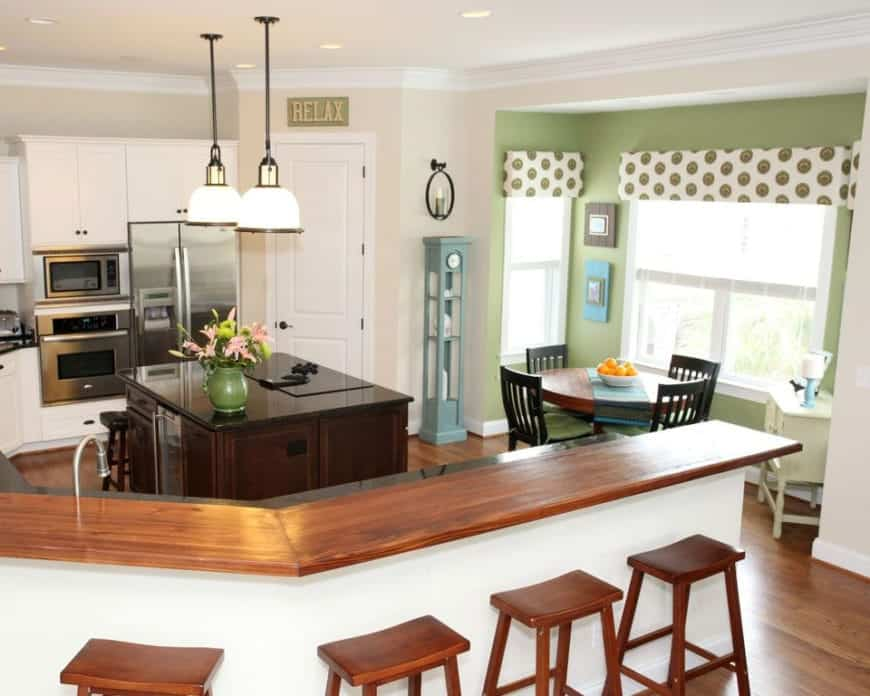Cottage kitchen accented with sage green walls and polka dots curtains. It includes a white curved peninsula topped with wood counter that matches the wooden bar stools.
