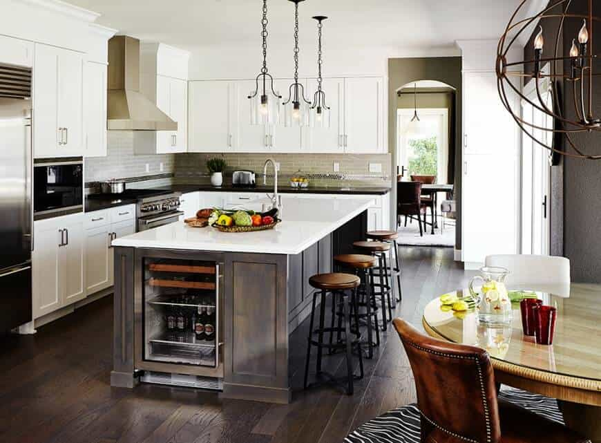 Round bar stools sit on a natural wood breakfast island that complements the hardwood flooring and topped with white marble counter. It is fitted with a built-in wine fridge and lighted by three glass pendants.
