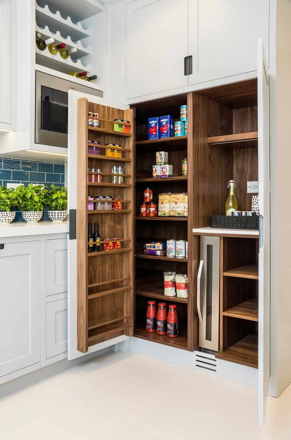 Sleek kitchen featuring a swing out pantry with natural wood internal and white cabinetry along with a built-in wine rack mounted above an oven shelf.