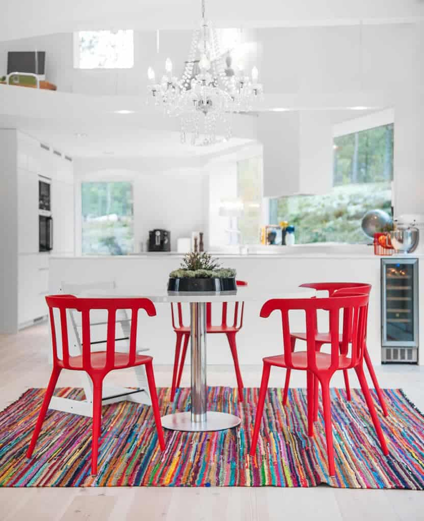 An elegant crystal chandelier illuminates the white kitchen accented with red chairs and colorful rug. It has a kitchen bar fixed with a built-in wine fridge.