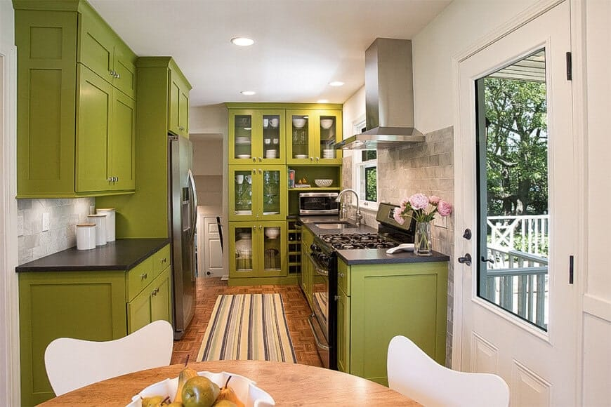 Mid-century kitchen boasts green cabinetry and a brown patterned flooring topped with a stripes runner. It includes a built-in wine rack beside the front glass cabinetry.