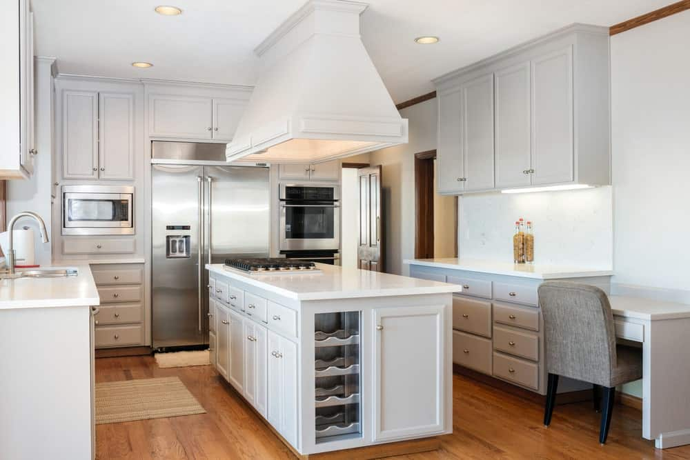 White kitchen accented with a hardwood flooring topped with tan rugs. It includes a range hood suspended over a breakfast island with built-in cooktop and wine rack enclosed with glass.