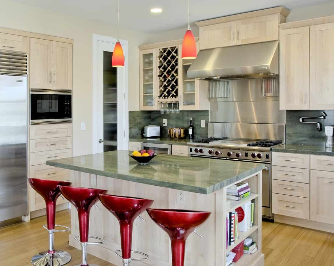 Fabulous kitchen boasts light wood cabinetry and breakfast island aligned with red bar stools. There's a built-in wine and rack with glassware holder sandwiched by front glass upper cabinets fixed above the marble backsplash.