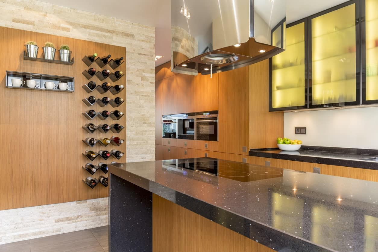 Modern kitchen features a brick accent wall fitted with a wood panel containing mounted wine rack and shelves.