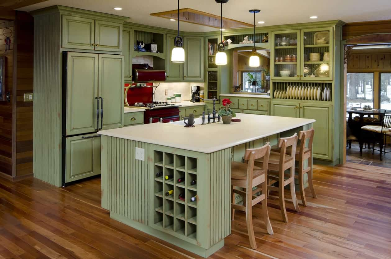 An open kitchen with mint green cabinetry and breakfast island illuminated by pendant lights. It has a white marble countertop and built-in wine rack.