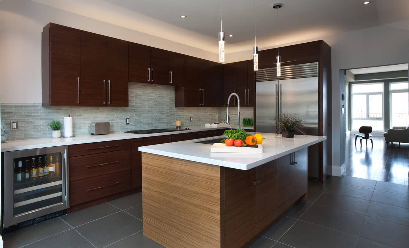 An L-shaped kitchen with a built-in wine fridge beside the dark wood cabinetry topped with pearl white marble counter.