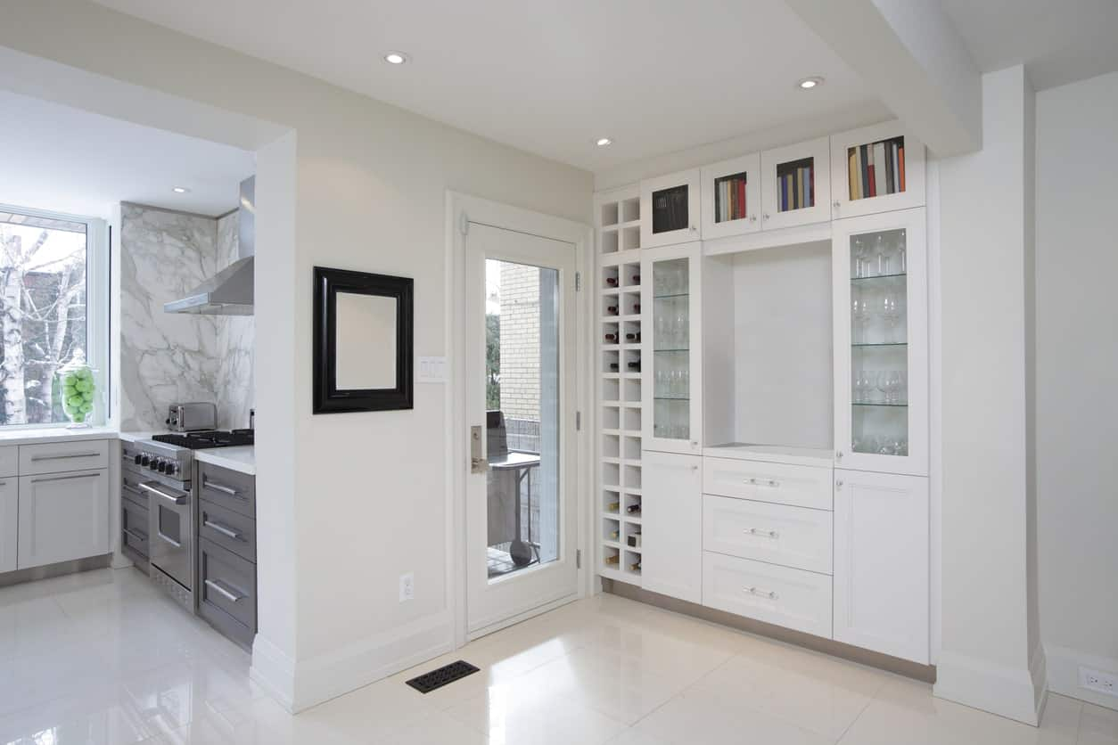 White kitchen features a separate built-in cabinet with glassware shelves enclosed in glass and wine rack on the leftmost side.