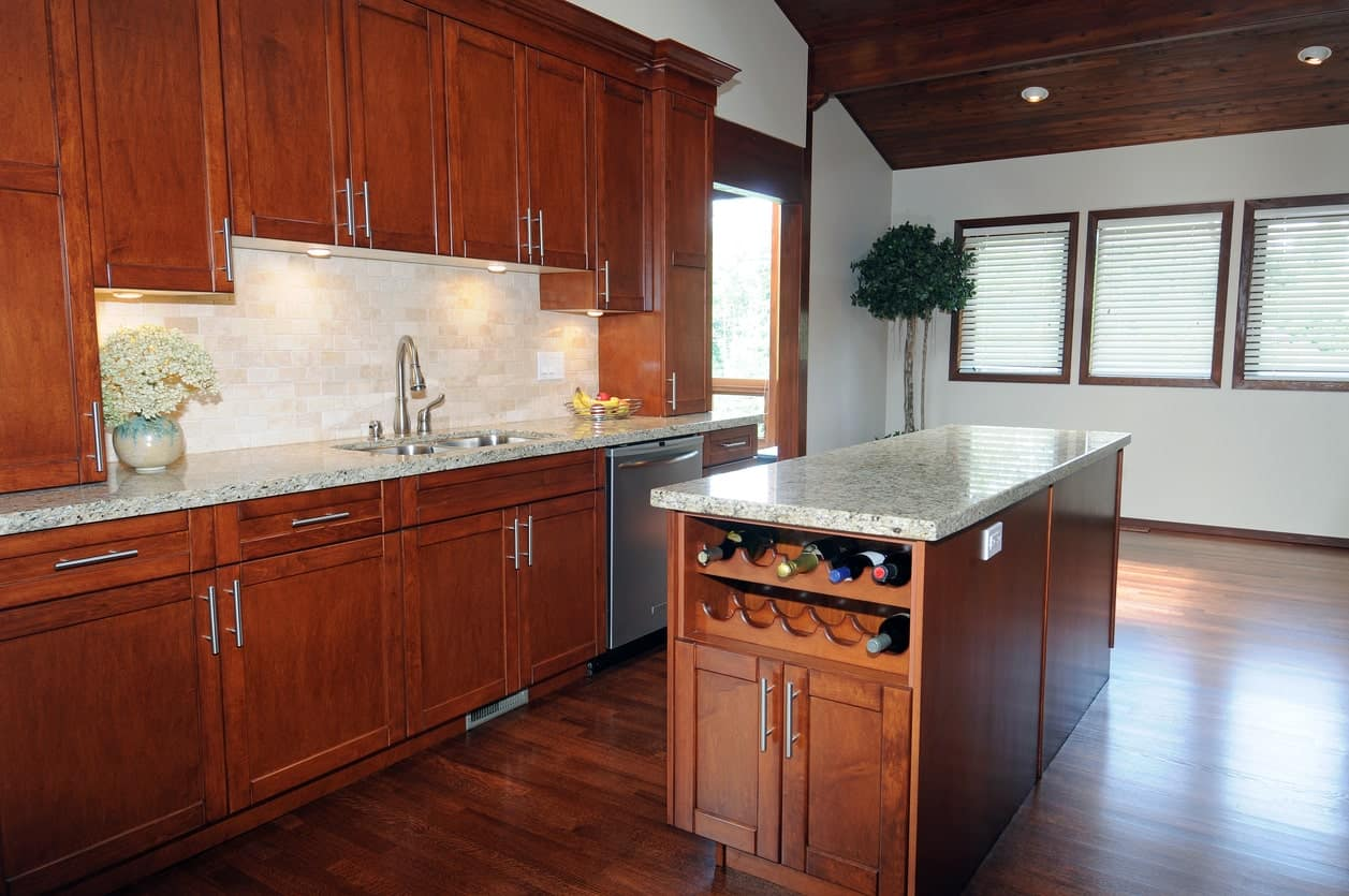 Kitchen with wood cabinetry and marble countertop complements the breakfast island. It has a wine rack fitted above the built-in cabinet.