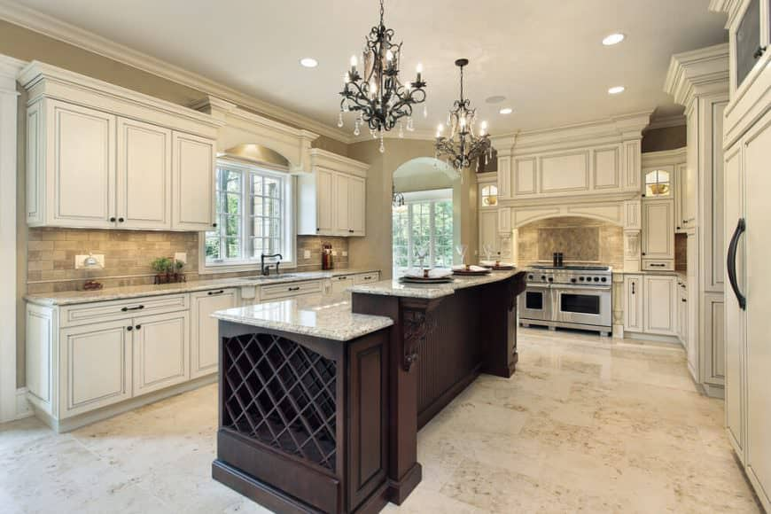 Elegant kitchen illuminated by vintage chandeliers that hung over a dark wood breakfast island. It is topped with gray marble counter and fitted with a built-in wine rack on its side.