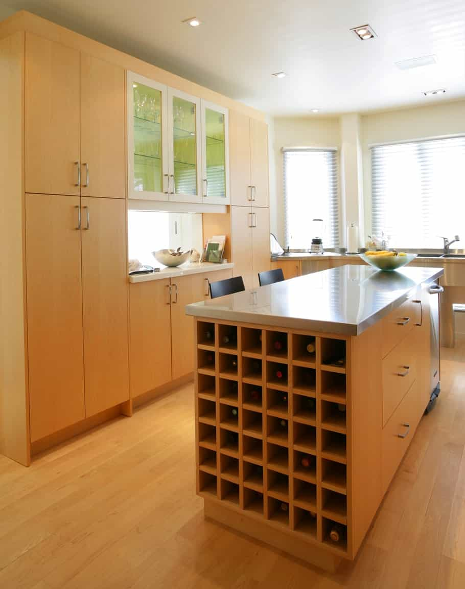 A wooden breakfast island topped with marble counter and matches the cabinetry is fitted with grid wine rack.