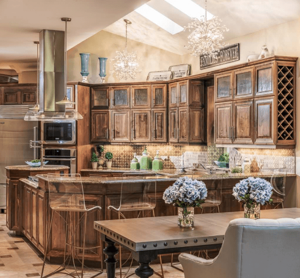 Glass bar chairs sit on the wooden kitchen counter topped with marble in this classic kitchen. It has upper natural wood cabinetry mounted with a built-in wine rack on its end.