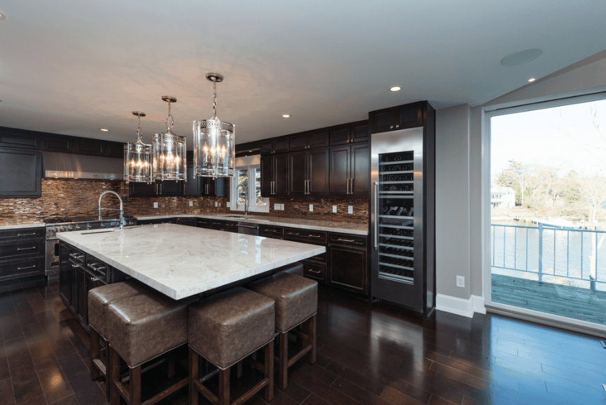 Dark kitchen lighted by fancy glass pendants that hung over a breakfast island with marble countertop and brown bar stools. It has dark wood cabinetry with a wine cooler to its edge.