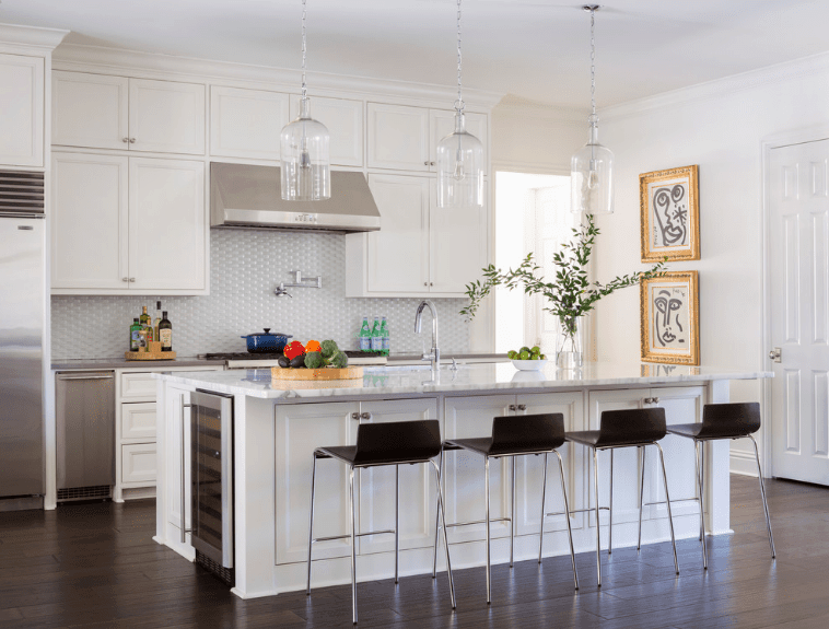 Black counter stools sit on a breakfast island with white marble countertop and built-in wine fridge on the side.