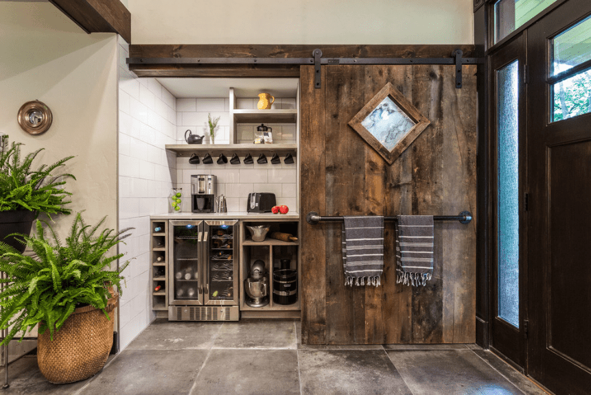 Rustic kitchen features a sliding wood plank panel against white brick tiles with floating shelves and built-in wine fridge.