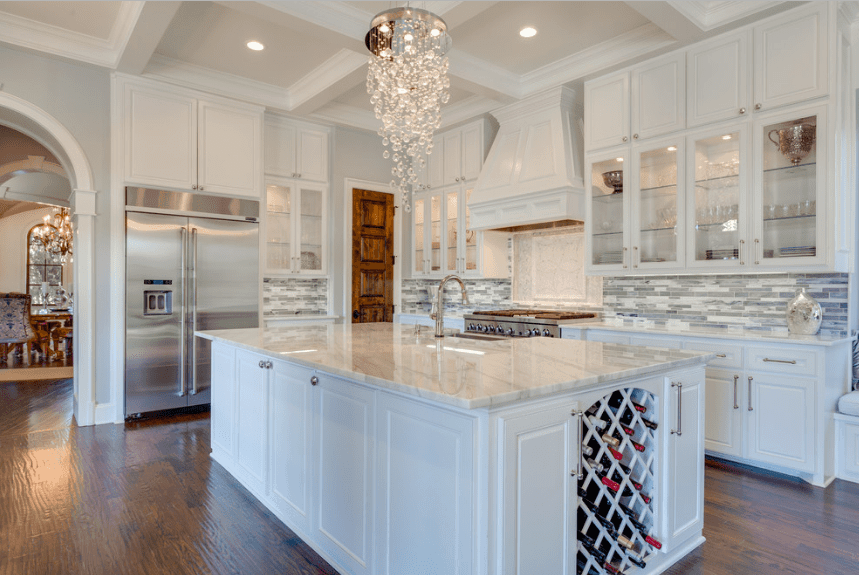 Fabulous kitchen illuminated with a fancy crystal chandelier that hung from a coffered ceiling over a breakfast island fitted with a crisscross patterned wine rack.