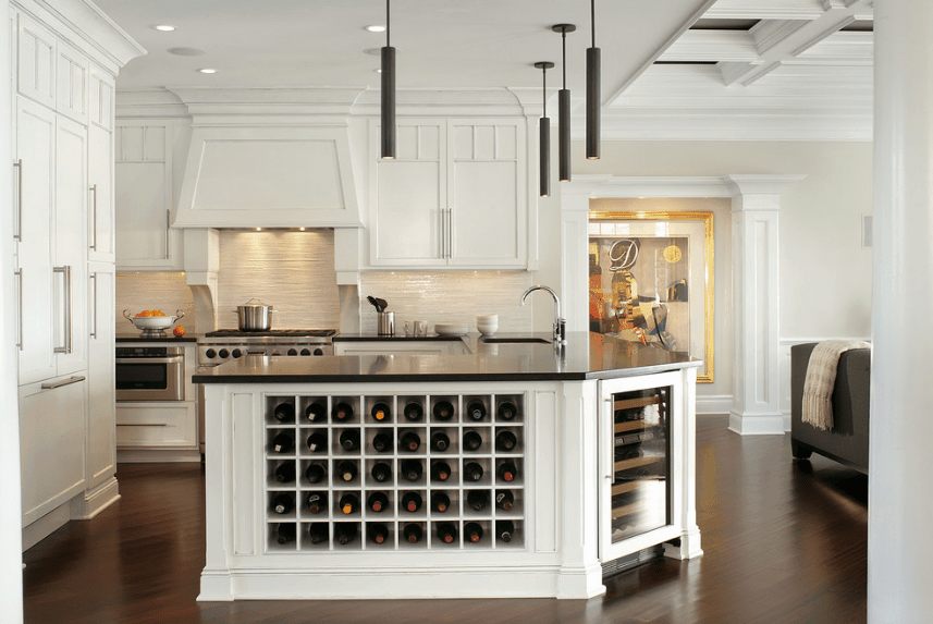 Traditional kitchen offers white cabinetry contrasted with black pendant lights and black granite countertop fitted on the U-shaped kitchen counter with built-in wine cubbies and wine fridge.