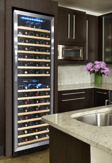 Kitchen with dark wood cabinetry along with marble countertop and backsplash integrated with a built-in wine cooler that features wood shelving.