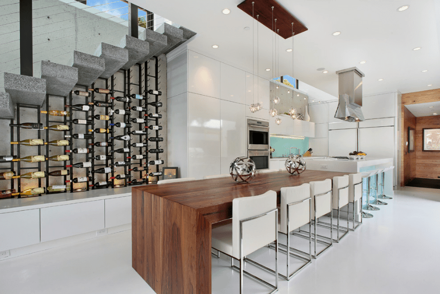 Modern kitchen displays vertical wines mounted on metal racks underneath a concrete staircase.