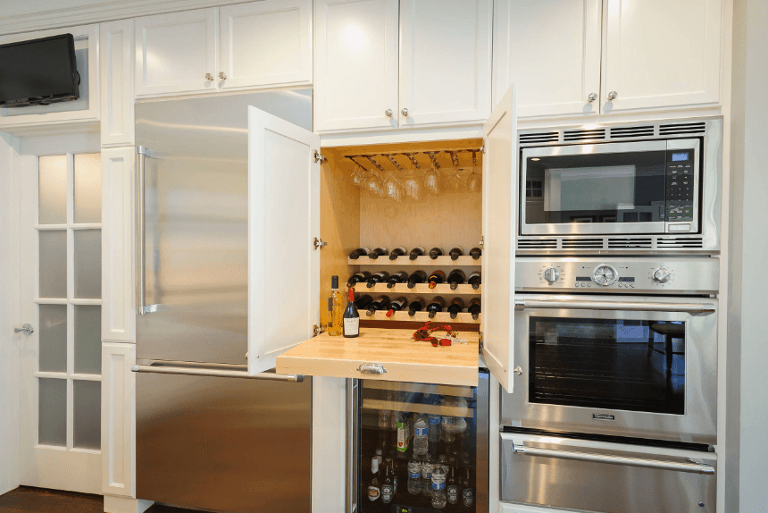White cabinetry fitted with stainless steel appliances and a wine shelf with wooden interior and pull-out above a beverage fridge.