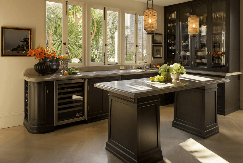 This kitchen showcases gray marble counter that's topped with a display cabinet and fitted with wine fridge along with dark wood cabinetry matching the breakfast island.