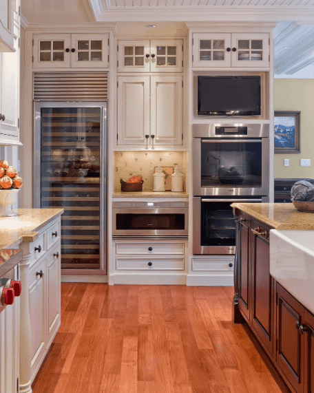 Kitchen surrounded with white cabinetry and stainless steel appliances including a wine cooler over hardwood flooring.