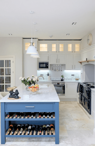 Clean white kitchen accented with a blue breakfast island that's topped with white marble counter and fitted with wine shelves.