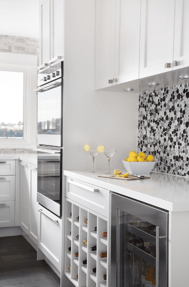 Contemporary kitchen boasts white cabinetry and wine cubbies mounted below a pull-out drawer and next to a beverage fridge. It is accented with a gorgeous black and gray patterned backsplash.