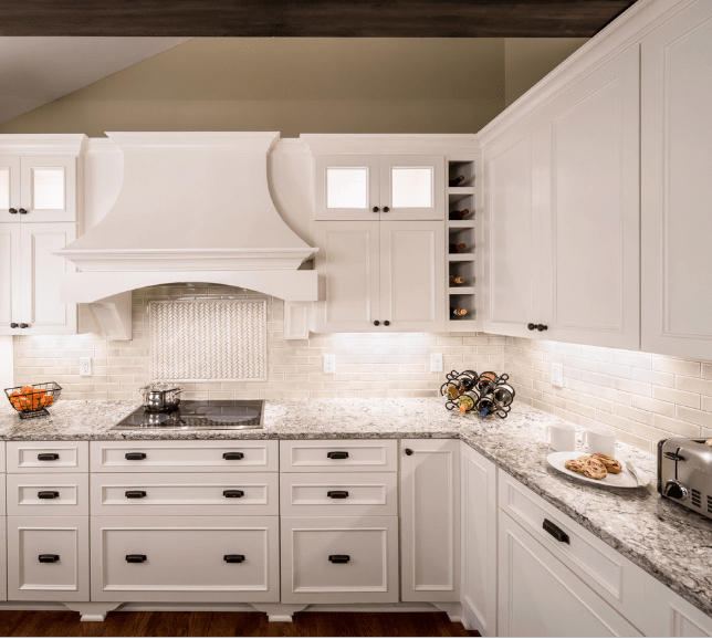 Elegant kitchen with white cabinetry fitted with a one column wine rack and gray marble countertop with built-in cooktop.