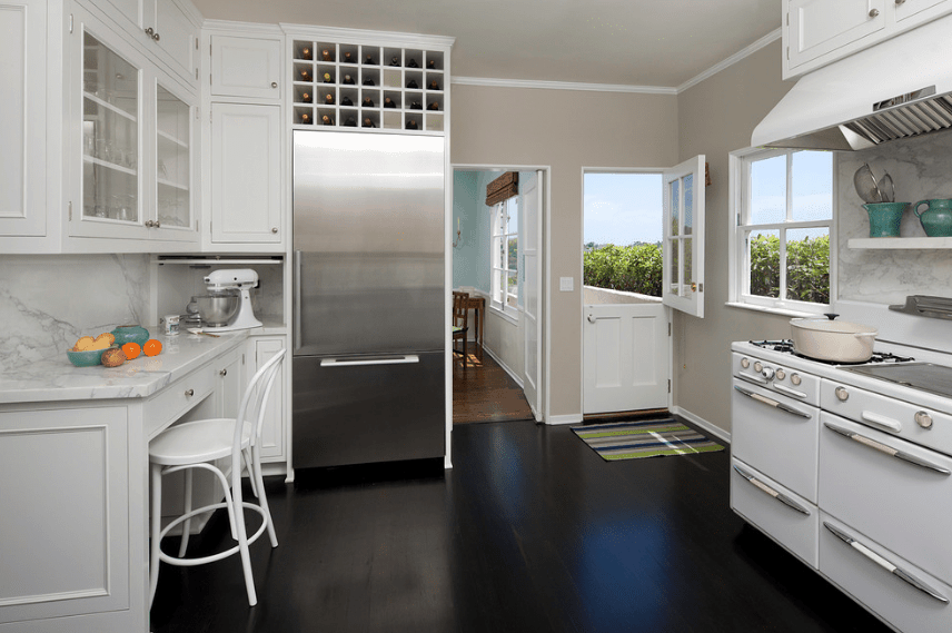 Traditional kitchen features dark hardwood flooring and white cabinetry along with a Dutch door. It includes built-in wine cubbies mounted above the refrigerator.