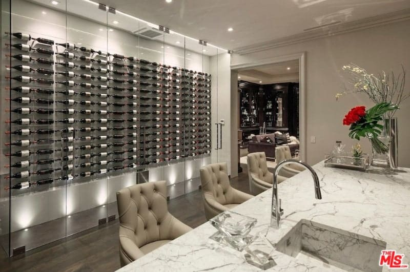 Elegant kitchen showcases a wine cellar enclosed in glass panels and displays vertical wines mounted on the white wall.