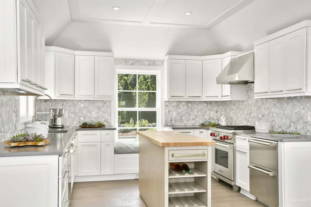 White kitchen accented with beautiful gray hex tiles backsplash. It boasts a seat nook fixed beneath a framed window and light wood breakfast island with built-in wine shelves.