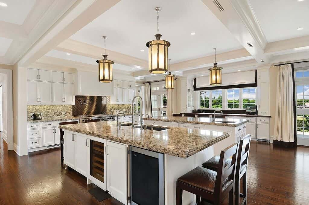 Fabulous kitchen offers a double breakfast island with marble countertops illuminated by lovely pendant lights. It is both fitted with sinks and chrome faucets. The larger one has a glass front built-in wine shelf and beverage fridge along with white cabinetry.