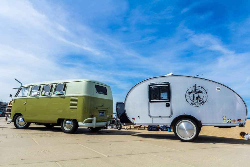 A teardrop trailer tied to a kombi van parked under a clear blue sky.