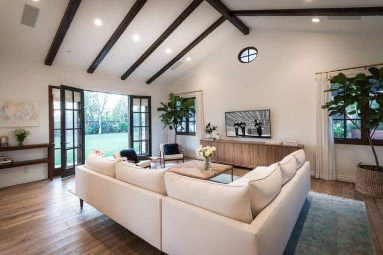 White living room lined with dark wood beams and illuminated by recessed ceiling lights. It includes wood framed windows and doors that bring fresh air and natural light in.