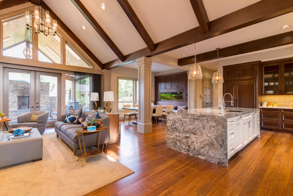 Sophisticated living room boasts a hardwood flooring and full height glazing along with wood cathedral ceiling.