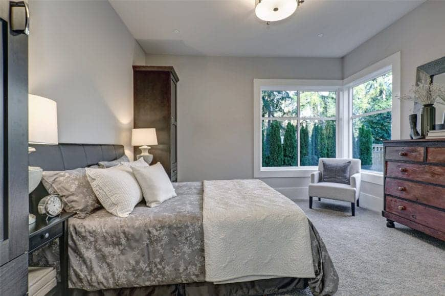 Gray primary bedroom with a leather bed that faces the rustic drawer next to the accent chair. It is lighted by a flush mount light and table lamps that sit on black nightstands.