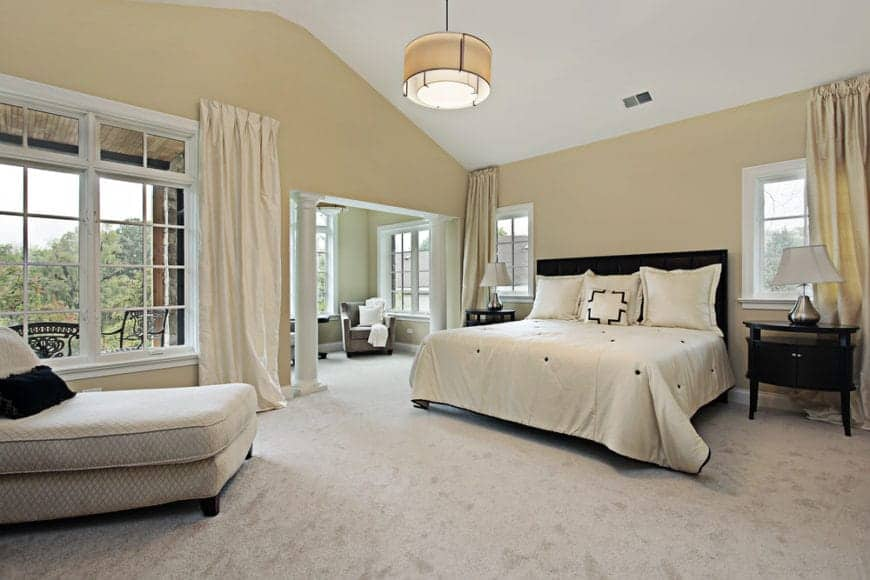 Spacious bedroom offers a carpet flooring and cathedral ceiling with a hanging semi-flush mount light. It includes a black bed dressed in beige bedding that complements with the draperies.