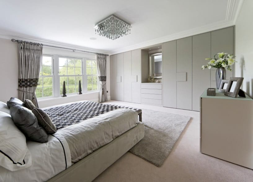Natural light streams through the glass windows in this primary bedroom featuring a gray velvet bed facing the full height wardrobe with a vanity in the middle.
