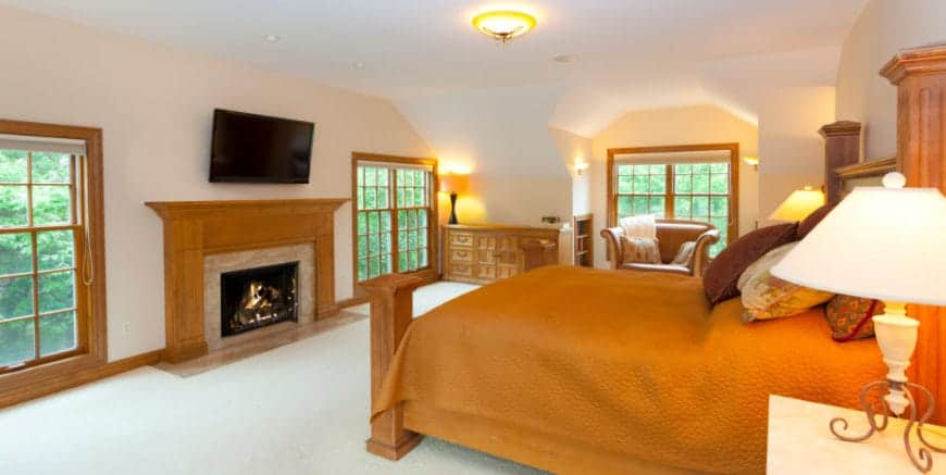 Warm primary bedroom surrounded by wooden framed glass windows fitted on the light peach walls with a fireplace and flat panel tv. It has a leather lounge chair and wooden bed dressed in orange bedding.