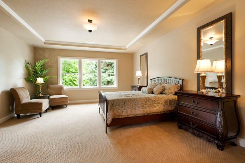 A semi-flush mount light illuminates this primary bedroom along with table lamps that sit on the dark wood nightstands topped with huge mirrors. It has a wooden bed and brown velvet seating in the corner accented with a potted plant.