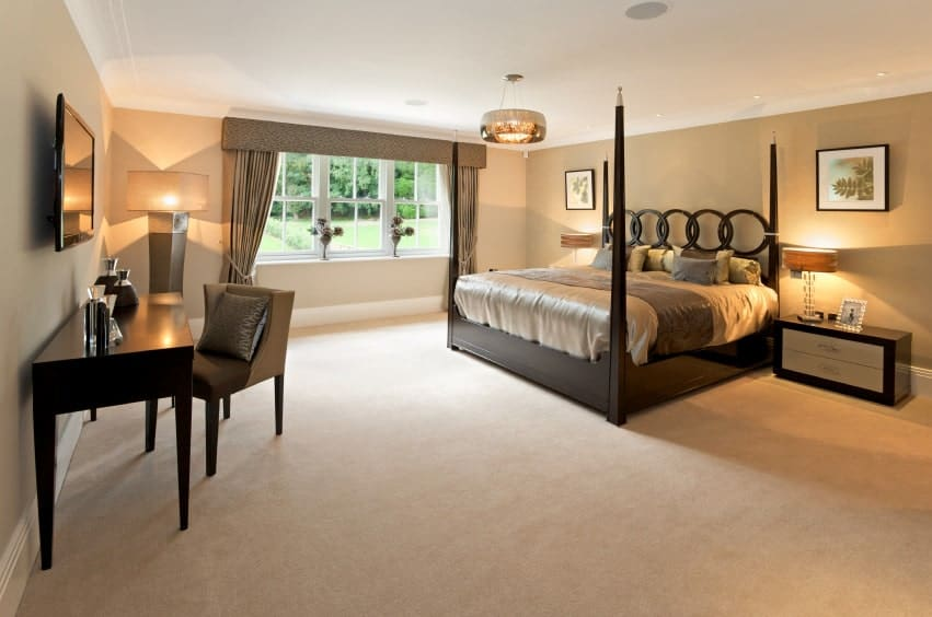 Contemporary master bedroom showcases a stylish black four poster bed and a wooden desk paired with a wingback chair.