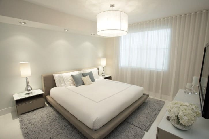 White primary bedroom with a low bed on gray rugs lighted by modern table lamps along with semi-flush mount light and recessed ceiling lights.