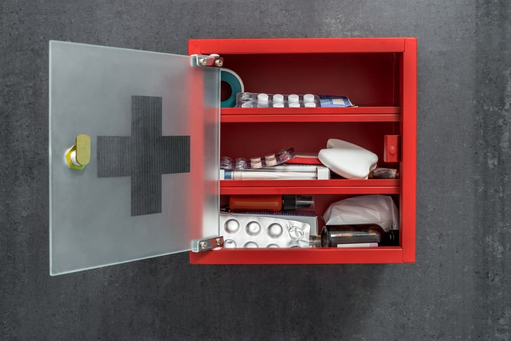 Open red medicine cabinet on a cement wall.