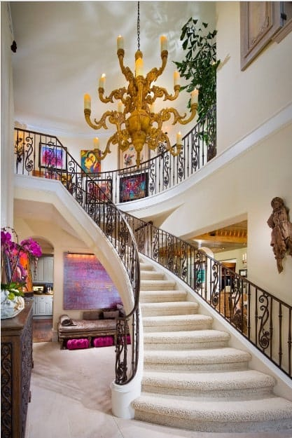 Mediterranean house filled with colorful artworks and a stairway covered in a beige carpet and framed with ornate railings. It is lighted by a huge fabulous candle chandelier.