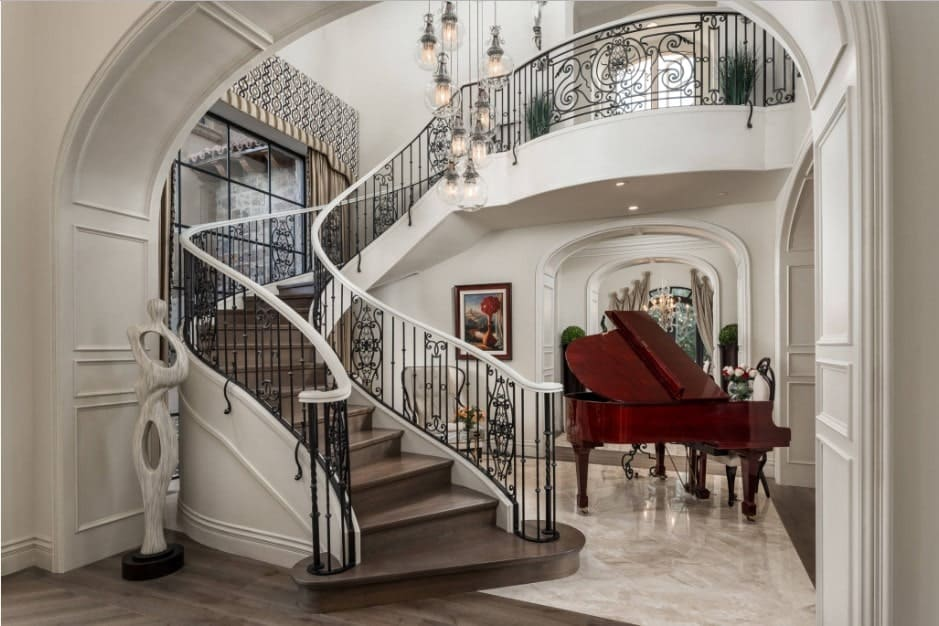 Elegant entryway with contemporary sculpture and baby grand piano along with a wooden staircase fitted with ornate wrought iron railings and illuminated by glass globe chandelier.
